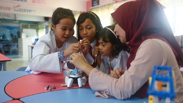 Asian elementary schoolgirls and female teacher building robot in science class