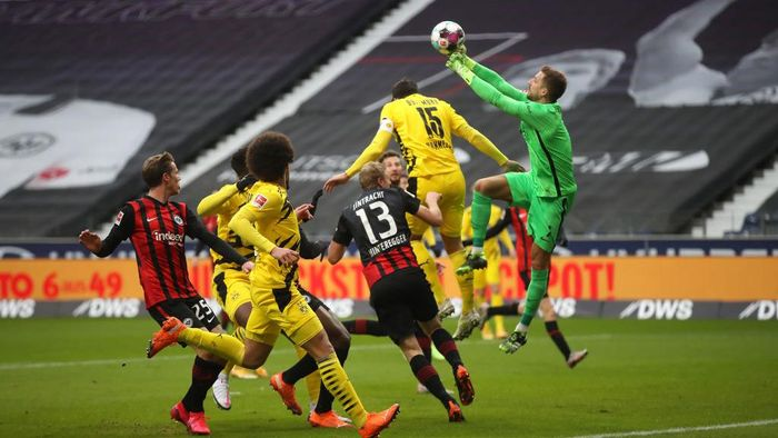 FRANKFURT AM MAIN, GERMANY - DECEMBER 05: Kevin Trapp of Eintracht Frankfurt punches the ball clear from Mats Hummels of Borussia Dortmund  during the Bundesliga match between Eintracht Frankfurt and Borussia Dortmund at Deutsche Bank Park on December 05, 2020 in Frankfurt am Main, Germany. Football Stadiums around Germany remain empty due to the Coronavirus Pandemic as Government social distancing laws prohibit fans inside venues resulting in fixtures being played behind closed doors. (Photo by Alex Grimm/Getty Images)