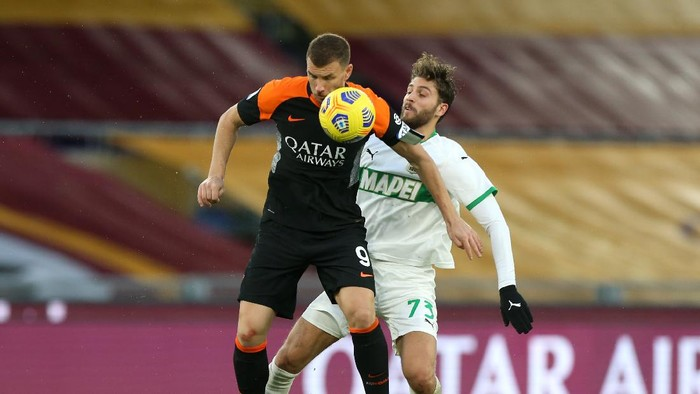 ROME, ITALY - DECEMBER 06: Manuel Locatelli of US Sassuolo battles for possession with Edin Dzeko of Roma during the Serie A match between AS Roma and US Sassuolo at Stadio Olimpico on December 06, 2020 in Rome, Italy. Sporting stadiums around Italy remain under strict restrictions due to the Coronavirus Pandemic as Government social distancing laws prohibit fans inside venues resulting in games being played behind closed doors. (Photo by Paolo Bruno/Getty Images)