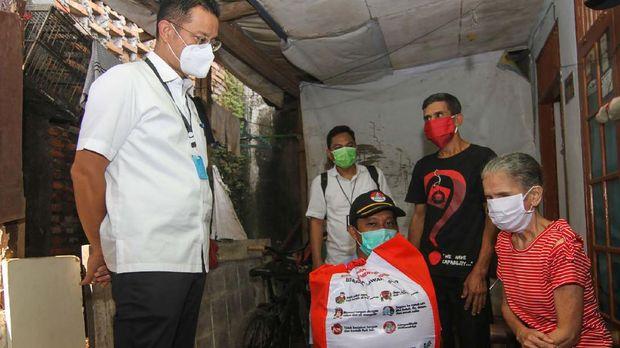 Menteri Sosial Juliari P Batubara (kiri) memberikan paket bantuan kepada warga terdampak COVID-19 di Beji, Depok, Jawa Barat, Kamis (14/5/2020). Sebanyak 123.881 paket sembako dari pemerintah pusat didistribusikan kepada masyarakat kurang mampu di Kota Depok guna meringankan beban ekonomi di tengah Pandemi COVID-19. ANTARA FOTO/Asprilla Dwi Adha/nz