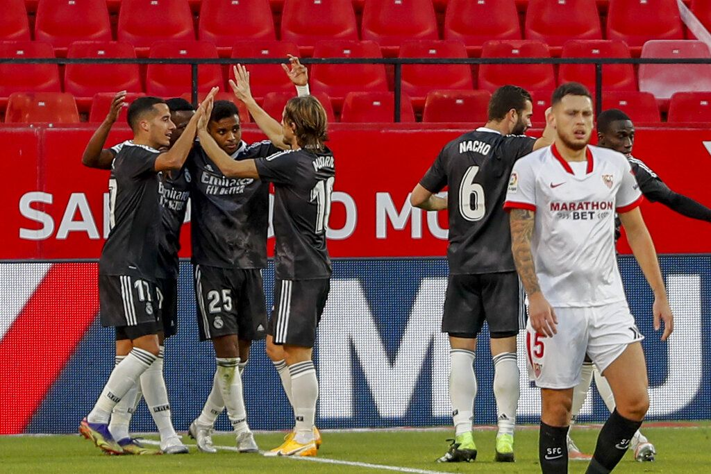 Real Madrid's players celebrate a goal during the Spanish La Liga soccer match between Sevilla and Real Madrid at the Ramon Sanchez Pizjuan stadium in Seville, Spain, Saturday Dec. 5, 2020. (AP Photo/Angel Fernandez)