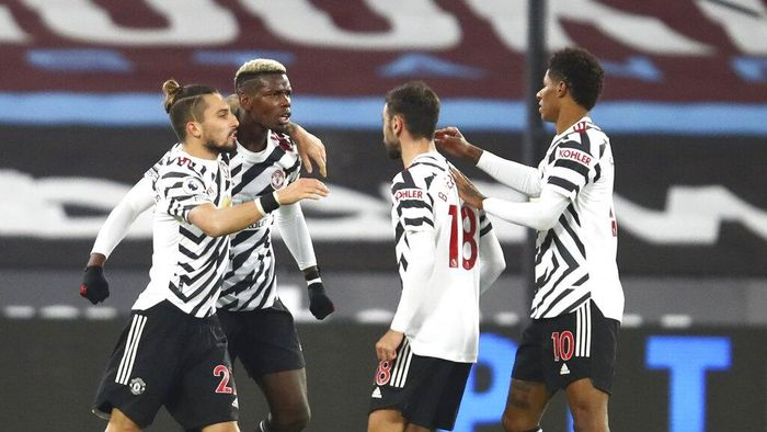 Manchester Uniteds Paul Pogba, second left, celebrates with teammates after scoring his sides opening goal during the English Premier League soccer match between West Ham United and Manchester United at the London stadium in London, England, Saturday, Dec. 5, 2020. (Julian Finney/Pool Via AP)