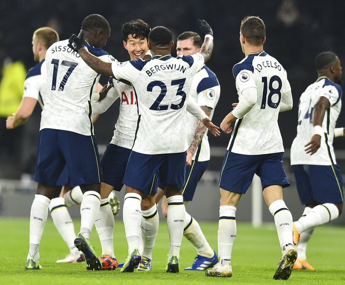 Tottenham players celebrate with Son Heung-min, third left, who scored his side's first goal during the English Premier League soccer match between Tottenham Hotspur and Arsenal at Tottenham Hotspur Stadium in London, England, Sunday, Dec. 6, 2020. (Glyn Kirk/Pool via AP)
