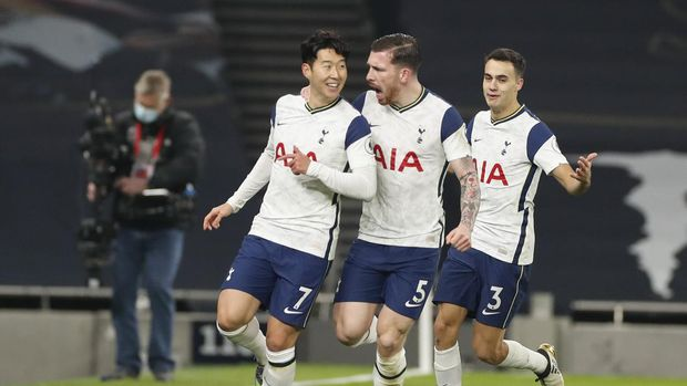 Tottenham's Sergio Reguilon, right, and Pierre-Emile Hojbjerg, center, celebrate with Son Heung-min, left, who scored his side's first goal during the English Premier League soccer match between Tottenham Hotspur and Arsenal at Tottenham Hotspur Stadium in London, England, Sunday, Dec. 6, 2020. (Paul Childs/Pool via AP)