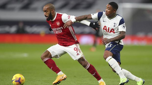 Arsenal's Alexandre Lacazette, left, and Tottenham's Steven Bergwijn vie for the ball during the English Premier League soccer match between Tottenham Hotspur and Arsenal at Tottenham Hotspur Stadium in London, England, Sunday, Dec. 6, 2020. (Catherine Ivill/Pool via AP)
