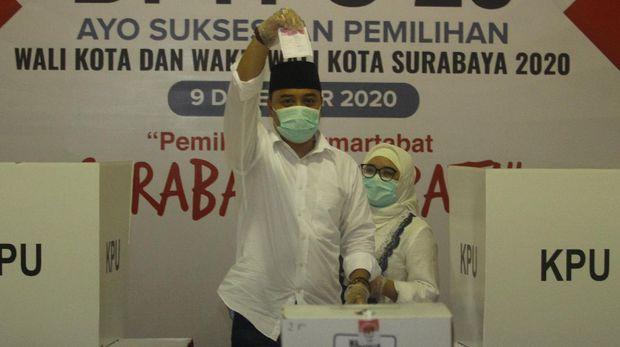 Calon Wali Kota Surabaya nomor urut 01 Eri Cahyadi (kiri) didampingi isterinya Rini Indriyani menunjukkan surat suara saat mencoblos di TPS 25, Ketintang Selatan, Surabaya, Jawa Timur, Rabu (9/12/2020). Pilkada Kota Surabaya 2020 diikuti dua pasangan calon yaitu Eri Cahyadi dan Armuji dengan nomor urut 01 serta pasangan Machfud Arifin dan Mujiaman dengan nomor urut 02. ANTARA FOTO/Moch Asim/wsj.