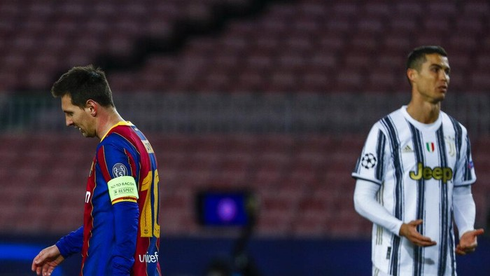 Barcelonas Lionel Messi, left, reacts next to Juventus Cristiano Ronaldo during the Champions League group G soccer match between FC Barcelona and Juventus at the Camp Nou stadium in Barcelona, Spain, Tuesday, Dec. 8, 2020. (AP Photo/Joan Monfort)