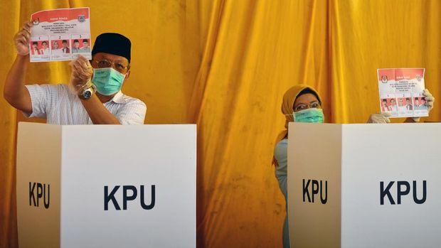 Calon Wali Kota Tangerang Selatan nomer urut tiga Benyamin Davnie (kiri) beserta istri menunjukan surat suara saat menggunakan hak pilihnya di TPS 16 Lengkong Karya, Serpong, Tangerang Selatan, Banten, Rabu (9/12/2020). Sebanyak 976.019 orang terdaftar dalam Daftar Pemilih Tetap (DPT) pada Pilkada Kota Tangerang Selatan 2020 yang diikuti tiga pasang calon Wali Kota dan Wakil Wali Kota Tangerang Selatan yakni nomor urut satu Muhammad - Rahayu Saraswati, nomor urut dua Azizah - Ruhamaben dan nomor urut tiga Benyamin Davnie - Pilar Saga Ikhsan. ANTARA FOTO/Muhammad Iqbal/wsj.