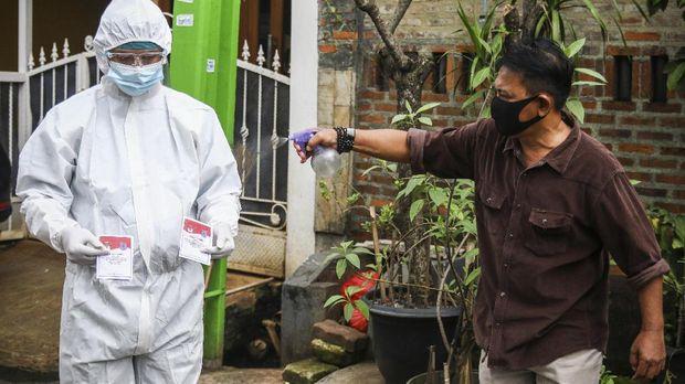 Petugas KPPS TPS 68 menyemprotkan cairan disinfektan kepada rekannya usai mengunjungi pemilih pasien COVID-19 dengan status Orang Tanpa Gejala (OTG) di Pondok Maharta, Tangerang Selatan, Banten, Rabu (9/12/2020). Untuk memenuhi hak pilih para pasien COVID-19 OTG pada Pilkada serentak 2020 di wilayah tersebut, petugas KPPS setempat melakukan jemput bola dengan tetap menerapkan protokol kesehatan. ANTARA FOTO/Rivan Awal Lingga/wsj.