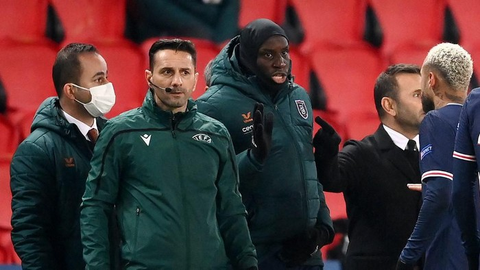 Romanian fourth official Sebastian Coltescu (2nd-L) looks on next to Istanbul Basaksehirs French forward Demba Ba (2nd-R) and Paris Saint-Germain Brazilian forward Neymar (1st-R) during the UEFA Champions League group H football match between Paris Saint-Germain (PSG) and Istanbul Basaksehir FK at the Parc des Princes stadium in Paris, on December 8, 2020. - Paris Saint-Germains decisive Champions League game with Istanbul Basaksehir was suspended on December 9 in the first half as the players walked off amid allegations of racism by one of the match officials. The row erupted after Basaksehir assistant coach Pierre Webo, the former Cameroon international, was shown a red card during a fierce row on the touchline with staff from the Turkish club appearing to accuse the Romanian fourth official of using a racist term. (Photo by FRANCK FIFE / AFP)