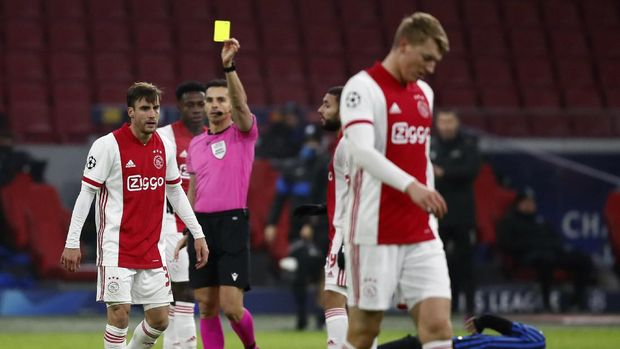 Referee Carlos del Cerro Grande shows a yellow card to Ajax's Nicolas Tagliafico during the group D Champions League soccer match between Ajax and Atalanta at the Johan Cruyff ArenA in Amsterdam, Netherlands, Wednesday, Dec. 9, 2020. (AP Photo/Peter Dejong)