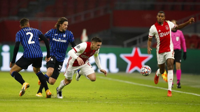 Ajaxs Dusan Tadic, centre, duels for the ball with Atalantas Rafael Toloi, left, and Atalantas Hans Hateboer during the group D Champions League soccer match between Ajax and Atalanta at the Johan Cruyff ArenA in Amsterdam, Netherlands, Wednesday, Dec. 9, 2020. (AP Photo/Peter Dejong)