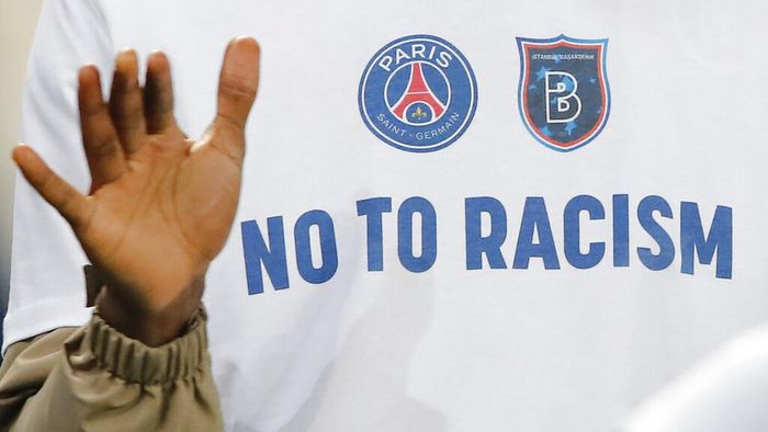 A No To Racism logo on the shirt of Basaksehir assistant coach Pierre Webo prior to the Champions League group H soccer match between Paris Saint Germain and Istanbul Basaksehir at the Parc des Princes stadium in Paris, France, Wednesday, Dec. 9, 2020. The match is resuming on Wednesday with a new refereeing team after players from Paris Saint-Germain and Istanbul Basaksehir left the field on Tuesday evening and didnt return when the fourth official — Sebastian Coltescu of Romania — was accused of using a racial term to identify Basaksehir assistant coach Pierre Webo before sending him off for his conduct on the sidelines. (AP Photo/Francois Mori)