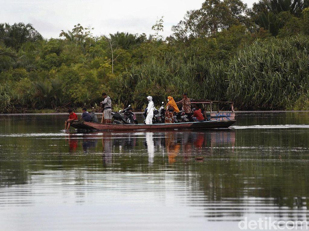 Begini Sensasi Naik Perahu Rakit Seberangi Sungai Sambas