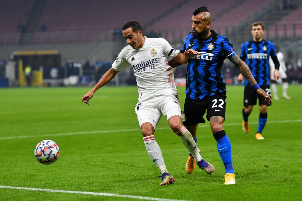 MILAN, ITALY - NOVEMBER 25: Lucas Vazquez of Real Madrid is challenged by Arturo Vidal of Inter Milan during the UEFA Champions League Group B stage match between FC Internazionale and Real Madrid at Stadio Giuseppe Meazza on November 25, 2020 in Milan, Italy. Football Stadiums around Europe remain empty due to the Coronavirus Pandemic as Government social distancing laws prohibit fans inside venues resulting in fixtures being played behind closed doors. (Photo by Valerio Pennicino/Getty Images)