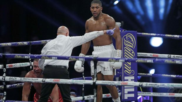 World Heavyweight boxing champion Britain's Anthony Joshua, right, knocks down challenger Bulgaria's Kubrat Pulev to win their Heavyweight title fight at Wembley Arena in London Saturday, Dec. 12, 2020. (Andrew Couldridge/Pool via AP)