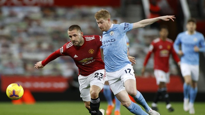 MANCHESTER, ENGLAND - DECEMBER 12: Luke Shaw of Manchester United and Kevin De Bruyne of Manchester City  battle for the ball  during the Premier League match between Manchester United and Manchester City at Old Trafford on December 12, 2020 in Manchester, England. The match will be played without fans, behind closed doors as a Covid-19 precaution. (Photo by Phil Noble - Pool/Getty Images)