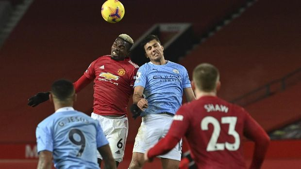 Manchester United's Paul Pogba, left, goes to head the ball with Manchester City's Rodrigo during the English Premier League soccer match between Manchester United and Manchester City at Old Trafford in Manchester, England. Saturday, Dec. 12, 2020. There have been 150 top-flight Man U v Man City derbies with United having won 58 and City 45, with 47 draws. (AP Photo/Paul Ellis/ Pool via AP)