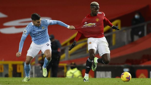 Manchester United's Paul Pogba has his shirt pulled by Manchester City's Ferran Torres of the English Premier League soccer match between Manchester United and Manchester City at Old Trafford in Manchester, England. Saturday, Dec. 12, 2020. There have been 150 top-flight Man U v Man City derbies with United having won 58 and City 45, with 47 draws. (AP Photo/Phil Noble/ Pool via AP)