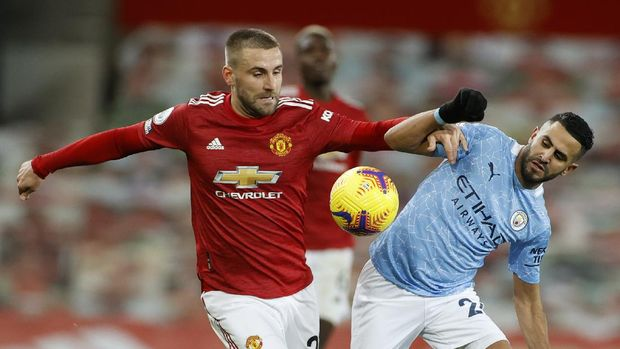 Manchester United's Luke Shaw, left vies for the ball with Manchester City's Riyad Mahrez of the English Premier League soccer match between Manchester United and Manchester City at Old Trafford in Manchester, England. Saturday, Dec. 12, 2020. There have been 150 top-flight Man U v Man City derbies with United having won 58 and City 45, with 47 draws. (AP Photo/Phil Noble/ Pool via AP)