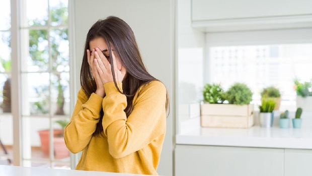 Beautiful young woman wearing yellow sweater with sad expression covering face with hands while crying. Depression concept.