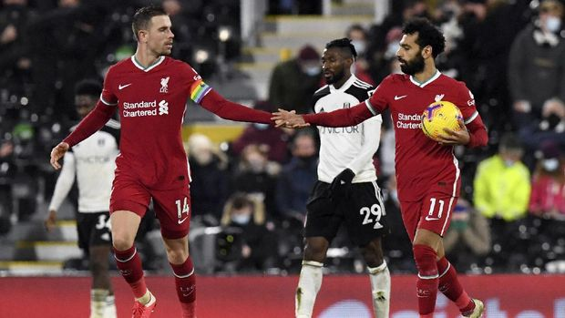 Liverpool's Jordan Henderson congratulates teammate Mohamed Salah after he scored a penalty during the English Premier League soccer match between Fulham and Liverpool, at Craven Cottage stadium, London, Sunday, Dec. 13, 2020. (Neil Hall/Pool via AP)