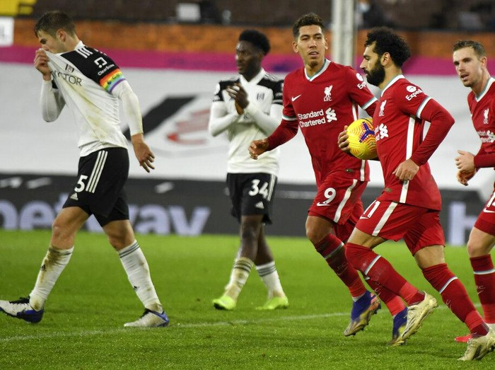 Liverpools Mohamed Salah retrieves the ball after scoring his sides first goal during the English Premier League soccer match between Fulham and Liverpool, at Craven Cottage stadium, London, Sunday, Dec. 13, 2020. (Mike Hewitt/Pool via AP)