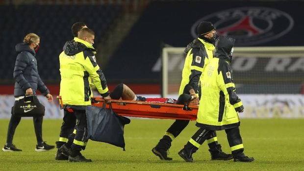PSG's Neymar, center, is carried off the field on a stretcher after getting injured during the League One soccer match between Paris Saint Germain and Lyon, at the Parc des Princes stadium in Paris, France, Sunday, Dec. 13, 2020. (AP Photo/Thibault Camus)