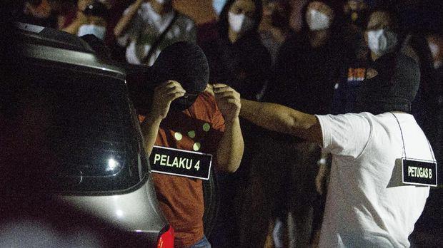 Sejumlah anggota tim penyidik Bareskrim Polri memperagakan adegan saat rekonstruksi kasus penembakan enam anggota laskar Front Pembela Islam (FPI) di Karawang, Jawa Barat, Senin (14/12/2020) dini hari. Rekonstruksi tersebut memperagakan 58 adegan kasus penembakan enam anggota laskar FPI di tol Jakarta - Cikampek KM 50 pada Senin (7/12/2020) di empat titik kejadian perkara. ANTARA FOTO/M Ibnu Chazar/aww.