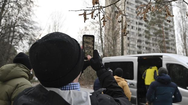 A visitor takes a smartphone picture of abandoned buildings in the ghost town of Pripyat, not far from Chernobyl nuclear power plant on December 8, 2020. - More than three decades after the Chernobyl nuclear disaster forced thousands to evacuate, there is an influx of visitors to the area that has spurred officials to seek official status from UNESCO. Officials hope recognition from the UN's culture agency will boost the site as a tourist attraction and in turn bolster efforts to preserve ageing buildings nearby. (Photo by GENYA SAVILOV / AFP)