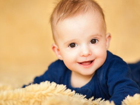 Cute baby boy with beautiful blue eyes on the white background