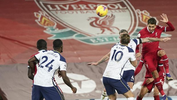 Liverpool's Roberto Firmino, right heads the ball and scores his sides 2nd goal of the game during the English Premier League soccer match between Liverpool and Tottenham Hotspur at Anfield in Liverpool, England, Wednesday, Dec. 16, 2020. (AP Photo/Jon Super)