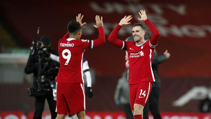 LIVERPOOL, ENGLAND - DECEMBER 16: Roberto Firmino and Jordan Henderson of Liverpool celebrate after the Premier League match between Liverpool and Tottenham Hotspur at Anfield on December 16, 2020 in Liverpool, England. A limited number of fans (2000) are welcomed back to stadiums to watch elite football across England. This was following easing of restrictions on spectators in tiers one and two areas only. (Photo by Clive Brunskill/Getty Images)