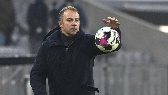 Bayern coach Hansi Flick catches the match ball during a German Bundesliga soccer match between Bayern Munich and RB Leipzig in Munich, Germany, Saturday, Dec. 5, 2020. (Sven Hoppe/dpa via AP)