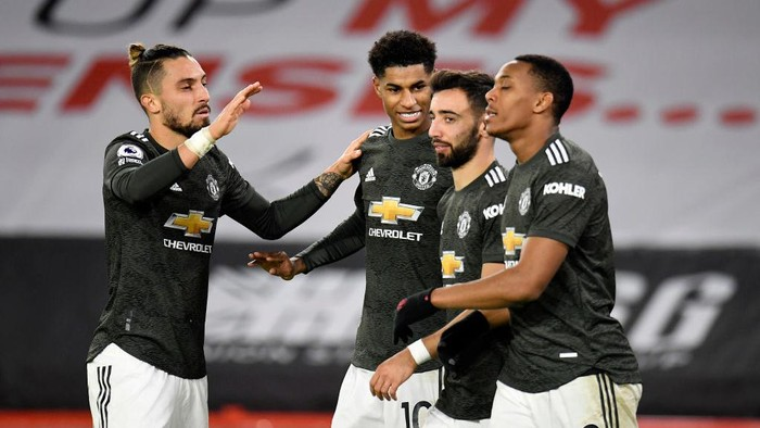 SHEFFIELD, ENGLAND - DECEMBER 17: Marcus Rashford of Manchester United celebrates with team mates (l - r) Alex Telles, Bruno Fernandes and Anthony Martial after scoring their sides third goal during the Premier League match between Sheffield United and Manchester United at Bramall Lane on December 17, 2020 in Sheffield, England. The match will be played without fans, behind closed doors as a Covid-19 precaution.  (Photo by Peter Powell - Pool/Getty Images)