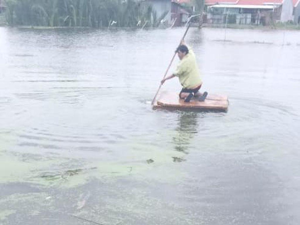 Viral Kurir di Makassar Tembus Banjir Pakai Rakit demi Antar Paket
