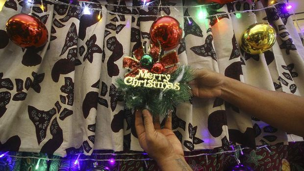Desainer Embran Nawawi menyelesaikan pembuatan pohon Natal berbahan kain batik Pamekasan di Surabaya, Jawa Timur, Kamis (3/12/2020). Pohon Natal setinggi 3,5 meter yang disusun dari 51 lembar kain batik tersebut sebagai upaya untuk melestarikan serta mempromosikan kain batik asal Kabupaten Pamekasan sekaligus memberikan sentuhan kebudayaan Nusantara dalam perayaan Hari Natal 2020. ANTARA FOTO/Moch Asim/aww.