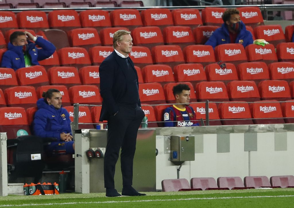 Barcelona's head coach Ronald Koeman watches his players from the side lines with Barcelona's Antoine Griezmann, left and Barcelona's Philippe Coutinho, right, behind in the substitutes area during the Spanish La Liga soccer match between Barcelona and Valencia at the Camp Nou stadium in Barcelona, Spain, Saturday, Dec. 19, 2020. (AP Photo/Joan Monfort)