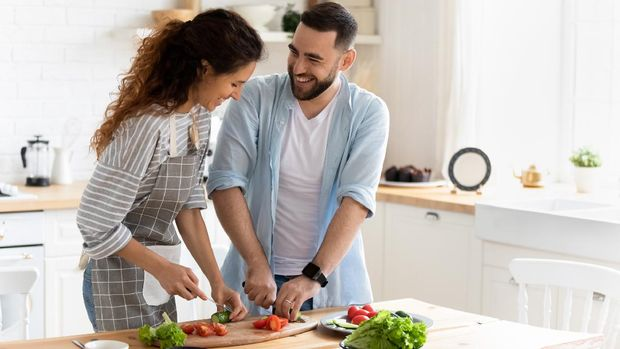 Happy couple standing in kitchen at home preparing together yummy dinner on first dating, spouses chatting enjoy warm conversation and cooking process, caring for health, eating fresh vegetable salad