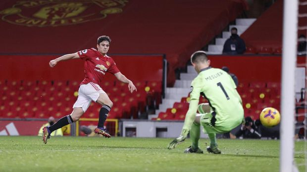 Manchester United's Daniel James, left, scores his side's fifth goal during an English Premier League soccer match between Manchester United and Leeds United at the Old Trafford stadium in Manchester, England, Sunday Dec. 20, 2020. (Clive Brunskill/Pool via AP)