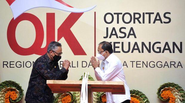 Ketua Dewan Komisioner Otoritas Jasa Keuangan (OJK) Wimboh Santoso (kiri) bersalam dengan Gubernur Bali Wayan Koster (kanan) saat peresmian gedung Kantor OJK Regional 8 di Denpasar, Bali, Senin (21/12/2020). Gedung Kantor OJK Regional 8 Bali dan Nusa Tenggara tersebut diharapkan dapat meningkatkan peran dan kontribusi OJK dalam meningkatkan pembangunan di daerah melalui hadirnya sektor keuangan. ANTARA FOTO/Fikri Yusuf/wsj.