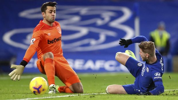 Chelsea's Timo Werner, right, slides towards West Ham's goalkeeper Lukasz Fabianski during the English Premier League soccer match between Chelsea and West Ham at Stamford Bridge, London, Monday, Dec. 21, 2020. (AP Photo/Clive Rose,Pool)