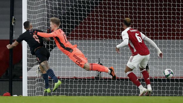 Manchester City's Gabriel Jesus, left, heads the ball past Arsenal's goalkeeper Runar Alex Runarsson to score his team's first goal during the English League Cup quarterfinal soccer match between Arsenal and Manchester City at Emirates Stadium, London, Tuesday, Dec. 22, 2020. (AP Photo/Frank Augstein)