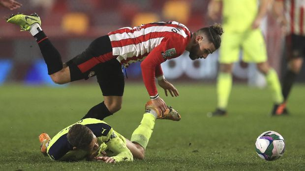 Brentford's Emiliano Marcondes, top, and Newcastle's Dwight Gayle challenge for the ball during the EFL Cup soccer match between Brentford and Newcastle United at Brentford Community Stadium in London, England, Tuesday, Dec. 22, 2020. (Adam Davy/Pool via AP)