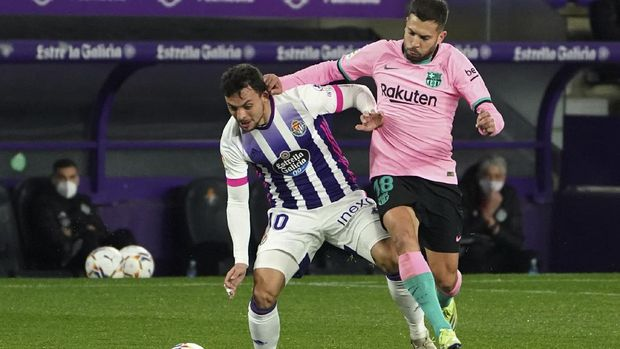 Valladolid's Oscar Plano, left, challenges for the ball with Barcelona's Jordi Alba during a Spanish La Liga soccer match between Valladolid and Barcelona at the Jose Zorrilla stadium in Valladolid, Spain,Tuesday Dec. 22, 2020. (Cesar Manso/Pool via AP)