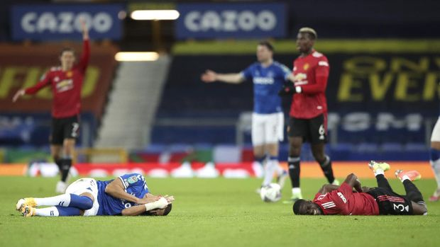 Everton's Richarlison, left, and Manchester United's Eric Bailly react after a collision during the English League Cup quarterfinal soccer match between Everton and Manchester United at Goodison Park, Liverpool, England, Wednesday, Dec. 23, 2020. (AP Photo/Nick Potts,Pool)