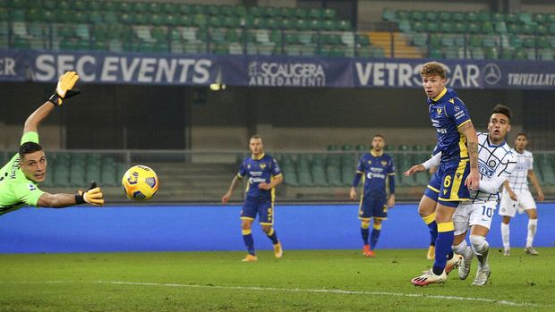 Inter Milan's Lautaro Martinez, right,  scores his side's opening goal during the Serie A soccer match between Verona and Inter Milan in Verona, Italy Wednesday, Dec. 23, 2020.  (Paola Garbuio/LaPresse via AP)