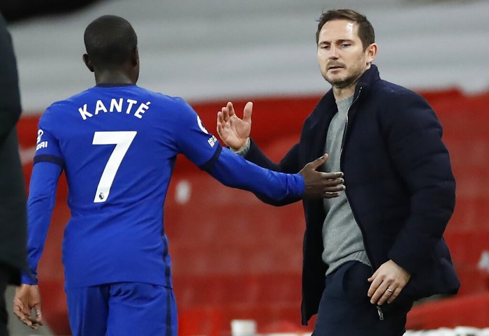 Chelseas NGolo Kante, left goes to shake hands with Chelseas head coach Frank Lampard as he is substituted during their English Premier League soccer match between Arsenal and Chelsea at the Emirates stadium in London, Saturday, Dec. 26, 2020. (Andrew Boyers/ Pool via AP)