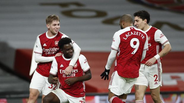 Arsenal's Bukayo Saka, second left, celebrates after scoring his sides 3rd goal of the game during their English Premier League soccer match between Arsenal and Chelsea at the Emirates stadium in London, Saturday, Dec. 26, 2020. (Andrew Boyers/ Pool via AP)