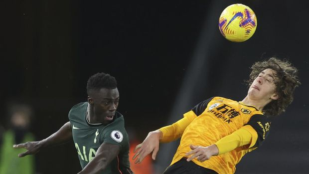 Tottenham's Davinson Sanchez, left leaps to head the ball with Wolverhampton Wanderers' Fabio Silva during the English Premier League soccer match between Wolverhampton Wanderers and Tottenham Hotspur at Molineux Stadium, in Woverhampton, England, Sunday, Dec. 27, 2020. (Carl Recine/ Pool via AP)
